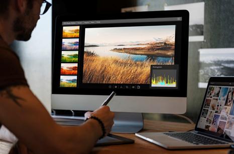 Description: Man editing photos on a computer Free Photo